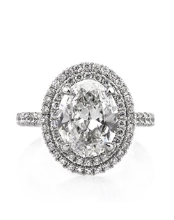 This remarkable oval cut diamond engagement ring will astonish you. The incredible 3.02ct oval cut diamond poised in the center of this astonishing custom-made ring is GIA certified at G-VVS2. It is exceptionally white and practically flawless! The cut is outstanding and it sparkles tremendously! It is accented by a double halo of round diamonds in a micropave setting. The combination is outstanding! There is a row of round diamonds set down the shank in a micropave setting as well. All of the diamonds are showcased beautifully with minimal metal showing. The center basket features round diamonds studded throughout the connectors as well. It is truly a work of art! You will love and cherish this piece forever!