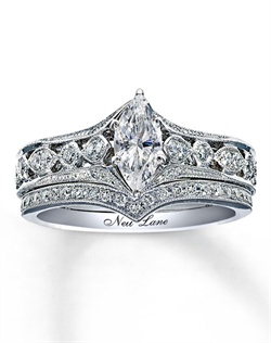 Neil Lane blends vintage Hollywood style with a brilliance that transcends time. A marquise diamond appears front and center in this engagement ring accented by a row of round diamonds on each side. Milgrain detail follows the line of the ring across the top and bottom, while hand-finished scrollwork is meticulously detailed along the sides. A classic chevron wedding band is the perfect complement. The total diamond weight of this fine jewelry wedding set from Neil Lane Bridal® is 7/8 carat. The Neil Lane signature appears on the inside of both 14K white gold rings.