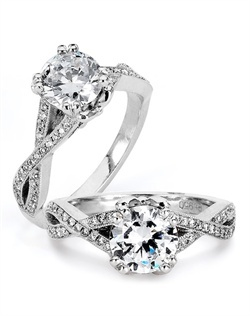 Infinitely feminine, this engagement ring designed by TRUE KNOTS® for the TRUE WOMAN® Engagement Ring Collection is sensual and inspired by the warmth of an embrace. Sparkling with 0.18tcw of round diamonds, it's sure to symbolize your eternal love. Matching wedding ring is available. Ring can accommodate any size round center (center not included). Available in platinum and gold.