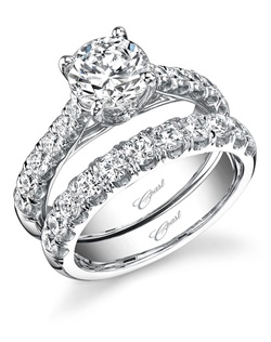 Graduated round diamonds grace the shoulders of this impressive engagement ring, with a band to match. A peek-a-boo diamond on the side of the head adds an exciting detail to this extraordinary wedding set. Total diamond weight .57CT, not including center stone. Created for a 1.25CT center stone in white gold or platinum. Matching band contains .75CT diamonds.