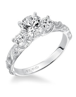 Diamond three stone engagement ring with round center, round side stones and a satin finished floral carving detail highlighted with diamonds.