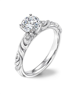 Diamond engagement ring with round center and a satin finished floral carving detail highlighted with diamonds