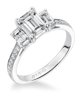 Diamond three stone engagement ring with emerald cut center stone, emerald cut side stones, and round diamond enhanced band.