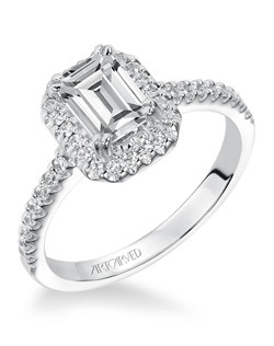 Diamond engagement ring with emerald cut center stone, round diamonds surrounding the center stone, and a diamond enhanced band.