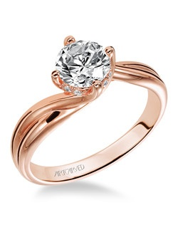 Diamond solitaire engagement ring with round center stone set in a Rose Gold twist setting.