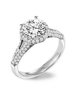 Diamond engagement ring with round center stone surrounded by round diamonds and a pave diamond enhanced band.