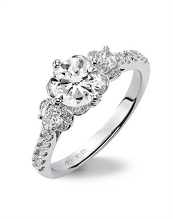 Three stone diamond engagement ring featuring an exclusive ArtCarved setting with prong set side diamonds and pave band.