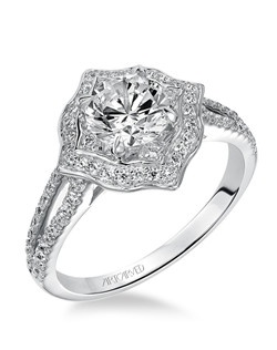 Contemporary Halo engagement ring featuring prong set diamond split shank.