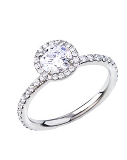 This solitaire halo platinum ring features a round Forevermark center diamond surrounded by pave diamonds.