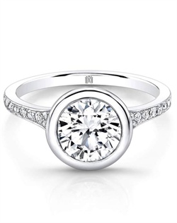Rahaminov&#39;s handmade diamond ring features a Forevermark round center diamond surrounded by a high polish bezel and complimented with 0.22 carats in melee on the band set in 18K white gold.