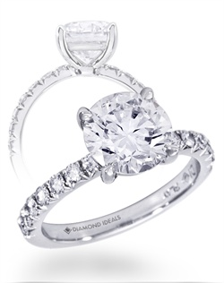 This custom ring features a 2.5 carat round center stone (not ncluded in quoted price) surrounded by approx. 0.35 carats of mêlée diamonds (1.8mm) and a tapered basket head. All rings can be order in any metal.
