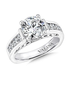 A brilliant center stone is highlighted by a row of large diamonds in a bright polished channel-setting. A surprise diamond and infinity filigree in the gallery are a delicate touch.  Mounting with side stones .70 ct. tw., 2 ct. round center.ds.