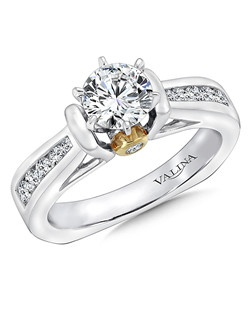 Channel-set round diamonds flank the center stone.  A surprize diamond accents the center stone for a glamorous finish. This engagement ring is part of the Modern Collection.  Mounting with side stones .34 ct. tw., 3/4 ct. round center. Price excludes center stone