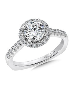 A crown of diamonds surround the round center stone. The raised diamond shoulders allow for a unique diamond finger rest. Round halo mounting  .35 ct. tw.,  1 ct. round center.Price excludes center stone