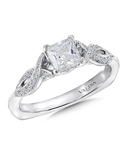 A delicate cross over design sets the stage for the dazzling Princess cut center. A unique finger rest is a pretty detail in the ring. Mounting with side stones .12 ct. tw., 5/8 ct. Princess cut center.Price excludes center stone