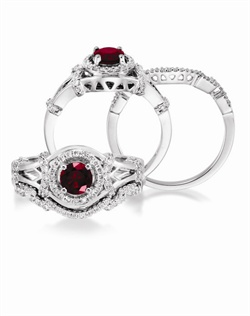 14K White Gold Ruby and Diamond Wedding Set. A 0.65ct round ruby is surrounded by 0.25cttw of round brillant diamonds. Available with matching wedding band with 0.11cttw of round brillant diamonds.