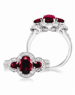 14k White Gold Ruby and Diamond Engagement Ring. A 1.55ct Oval Ruby is flanked by two .40cttw pear shaped rubies and .32 cttw of round brillant diamonds.