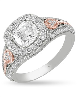 The pillow soft rounded edges of this old style cushion halo ring are defined by delicate milgrain edging.  A 1.0ct cushion center stone and 0.58cts of Ideal Cut diamonds, F-G Color, SI1 Clarity are set in 14Kt White, Pink, and/or Yellow Gold.  The center stone and matching wedding band are sold separately.
