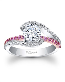 This classic white gold diamond engagement ring features a prong set round center. The split shank is adorned with shared prong set diamonds and the shoulders curve up to cradle the center. A pink sapphire bridge graces the center. Also available in yellow gold, rose gold, 18k and Platinum.
