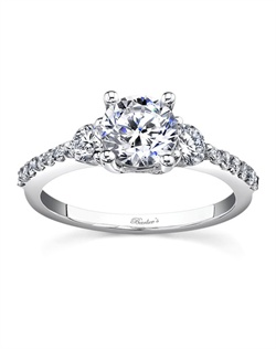 Classic elegance with clean lines, this three stone diamond engagement ring, features diamond accent stones flanking the prong-set round diamond center. The dainty shoulders are accented with shared prong set diamonds adding the finishing touch of elegance to this unique ring. Also available in rose gold, yellow gold, 18k and Platinum.