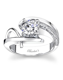 This modern unique engagement ring has a white gold by pass shank that curves around the prong set diamond center. One shoulder is accented with pave set diamonds decorating the inside wall, while the other shoulder has a round wire trim rising from the bottom of the shank and meeting at the top. Also available in rose gold, yellow gold, 18k and Platinum.