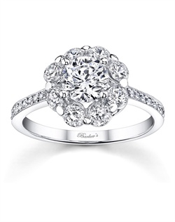 Stunning, in vogue, this white gold diamond halo engagement ring will capture the eye of many admirers. Shared prong set diamonds encircle the low profile round diamond center and pave set diamonds cascade down the dainty shank for a look of sheer elegance. Also available in rose gold, yellow gold, 18k and Platinum.