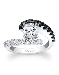 This unique black and white diamond engagement ring features a white gold split shank. A prong set round diamond center is cradled in the open center and one band sports black diamonds, while the other is adorned with white diamonds for a dramatic effect that is nothing short of spectacular. Also available in rose gold, yellow gold, 18k and Platinum.
