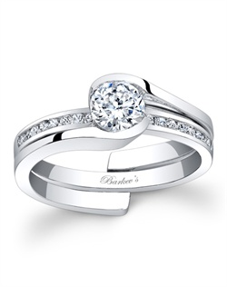 Capture the moment with this stylish, versatile, white gold diamond bridal set. The diamond engagement ring features a channel set round diamond center with an interlocking shank. The diamond wedding band sports channel set diamonds that can be worn alone for a casual look or can be slipped into the interlocking shank of the engagement ring for a luxurious look for everyday or special occasions. Also available in rose gold, yellow gold, 18k and Platinum.