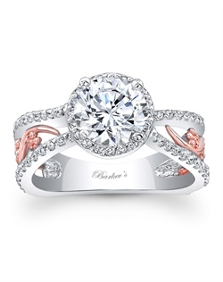 This bold and elegant two tone split shank halo engagement ring features a prong set round diamond center. The center halo and shoulder ridges are graced with shared prong set diamond, while a rose gold filigree adorns the center sides for a touch of drama. Also available in rose gold, yellow gold, 18k and Platinum.