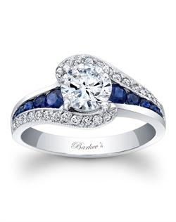 This classic white gold sapphire and diamond engagement ring features a prong set round diamond center. The shoulders split and curve up to cradle the center with pave set diamonds, while channel set saphiress grace the center on the sides. Also available in rose gold, yellow gold, 18k and Platinum.