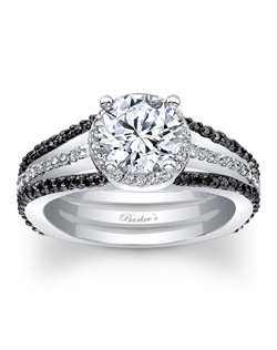 This unique, black and white diamond halo engagement ring features a prong set round diamond center encircled with diamonds, the white gold split shank sports shared prong set black diamonds on the outer ridges for an extra touch of drama. Also available in rose gold, yellow gold, 18k and Platinum.