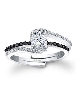 This classic white gold interlocking diamond wedding ring set, features a prong set round diamond center. The engagement ring is set with pave set diamonds and splits to allow the pave set black diamond wedding band to slip into the engagement ring under the center. Also available in rose gold, yellow gold, 18k and Platinum.