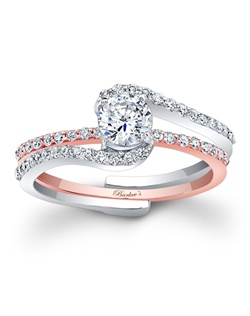 This classic two tone rose and white gold interlocking diamond wedding ring set, features a prong set round diamond center. The white gold engagement ring is set with pave set diamonds and splits to allow the pave set rose gold diamond wedding band to slip into the engagement ring under the center. Also available in white gold, yellow gold, 18k and Platinum.