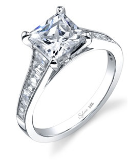 This dazzling 18K white gold diamond engagement ring features a 1 carat princess cut center diamond. Accentuated by surrounding round diamonds and baguette diamonds down the shank, designed to enhance the center diamond, contains a total 0.63 carats. The diamond engagement ring is available in any shape or size center diamond, in 18K white gold or platinum, with a flush fit wedding band to match.