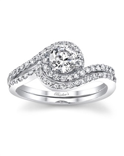 This diamond bridal set features shared prong set diamonds. The diamond engagement ring is set with a prong set round diamond center, shared prong set diamonds swirl around the center and cascade down the shoulders. The diamond wedding ring mirrors the engagement rings walls and sits up close beside it. Also available in white gold, yellow gold, 18k and Platinum.