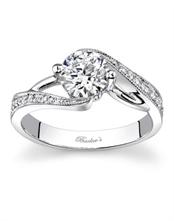 This modern version of the vintage bypass ring has a channel set round diamond center with balancing prongs for added protection. Pave set diamonds cascade down the shoulder and a white gold wire accent rises from the shoulders and disappears into the center head on both sides; a milgrain finish adds a touch of glam. Also available in 18k and Platinum.