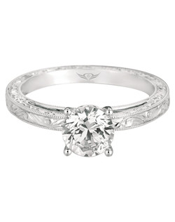 FlyerFit® Vintage Engagment ring in 14K White Gold. Artistic and stunning, make an entrance with this Modern take on a Vintage idea. Featuring a delicate Hand Engraved band and a Single Center Stone, the spotlight will be on you as you as he places this elegant beauty on your finger. Swhon here with a Round Center Stone. All FlyerFit® rings feature Hearts and Arrows diamonds.