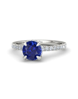 Simply stunning, this ring's round brilliant gem is perfectly complemented by a delicate and feminine band with gems half-way around the finger. More gems surround the side of the center stone. All you'll see from every angle is dazzling brilliance. Customize with your choice of 25 gemstones and 9 precious metals.
