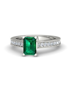 A gorgeous, emerald-cut center stone is flanked by a accent gems set into the band. Tastefully stunning. Customize with your choice of 26 gemstones and 9 precious metals.