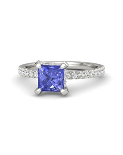 This ring's stunning, princess-cut gem is perfectly complemented by a delicate and feminine band with gems half-way around the finger. More gems surround the side of the center stone. All you'll see from every angle is dazzling brilliance. Customize with your choice of 26 gemstones and 9 precious metals.