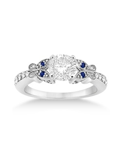 A total of 4 blue sapphires and 12 diamonds are showcased in this vintage style diamond and blue sapphire engagement ring. The bright diamonds are of GH Color, VS Clarity. This natural colored gemstones are hand set in a 18kt White Gold pave setting.