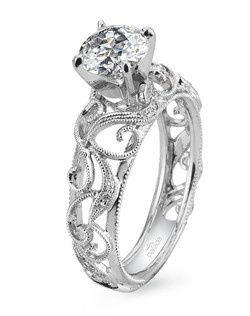 This vintage-inspired design Is anything but your basic engagement ring as milgrain etched scrolls  curl  and climb toward a show-stopping round-cut diamond.(0.11 ct tw) Available in platinum, 18K white, 18K yellow, or 18K rose gold. All Parade Design styles can be customized upon request.