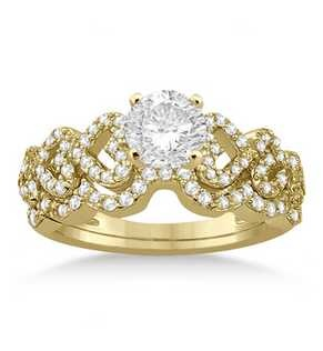 A spectacular bridal set crafted from 14 karat yellow gold that features approximately 87 round-cut, pave-set diamonds in a sparkling heart-shaped arrangement. The matching wedding band is contoured to fit the engagement ring.  Design your own engagement ring by choosing a center stone from our wide selection of conflict-free diamonds. This unique bridal set is available in a variety of metals.