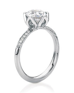 Round brilliant cut engagement ring named after the Scottish wildflower Bluebell. A fresh and floral bud-like solitaire with 5 petal-shaped prongs, available plain or with pavé diamond accents on the shank.