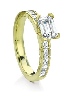 Stunning emerald-cut solitaire from the CAVA series, named after the Scottish Island of Cava. Scalloped edge shank sets an elegant line of emerald-cut side diamonds, complementing the delicate curved 4-prong emerald-cut center.