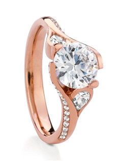 Gorgeous brilliant-cut engagement ring named after the Scottish Wildflower Poppy. Treasured for its beautiful, billowy petals, Poppy's center stone is accented with two flush-set pear shape diamonds and pave-set diamonds on the shank