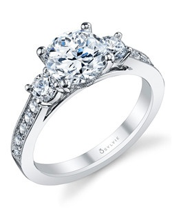 This vintage three-stone diamond engagement ring features a 1.5 carat round center with 0.57 total weight in diamonds.