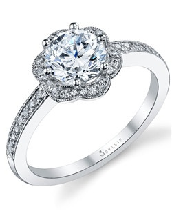 A gorgeous platinum diamond engagement ring that features a 1 carat round brilliant center diamond surrounded by beautiful diamond petals and a shank accentuated with a total .20 carats.
