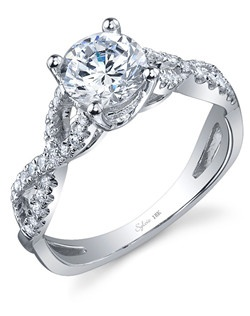 This dazzling 18K white gold diamond engagement ring features a 1.00 carat round brilliant center diamond. Beautifully designed to accentuate the center diamond, this engagement ring has a total of 0.26 carats of round diamonds flowing down this uniquely designed shank setting.