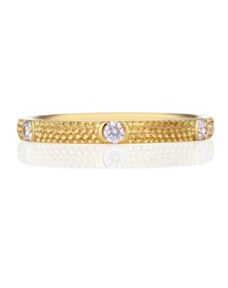 Effortlessly elegant and symbolic of something new and fresh, this yellow gold band features six round brilliant diamonds in a half-bezel setting. Band width 2mm. Total carat weight 0.18.